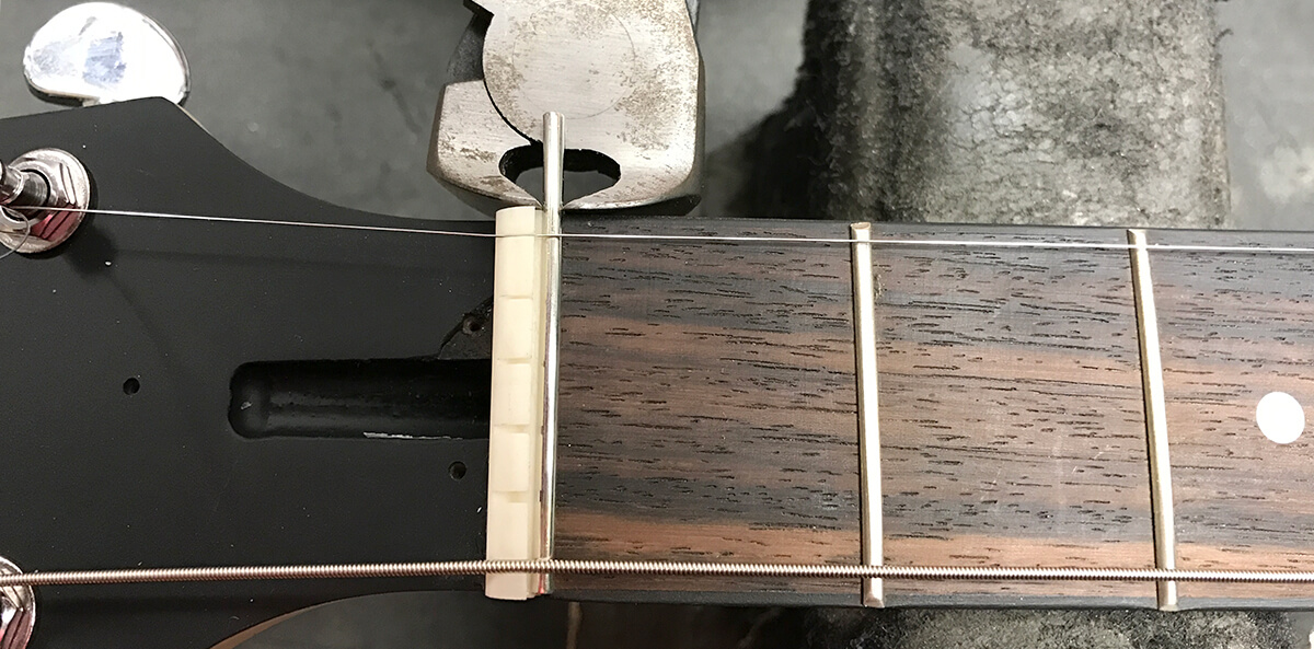 With the fret still in the Zero Glide nut, use wire snippers to cup away the excess fret material.