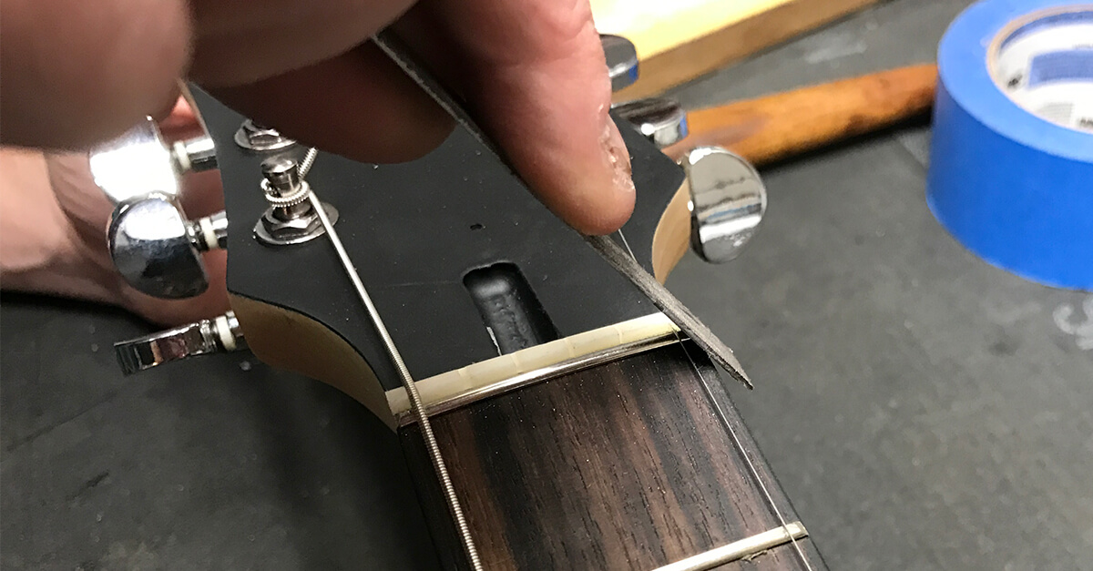 Using a thin metal file or sanding block, sand the fret to match the width of the nut.