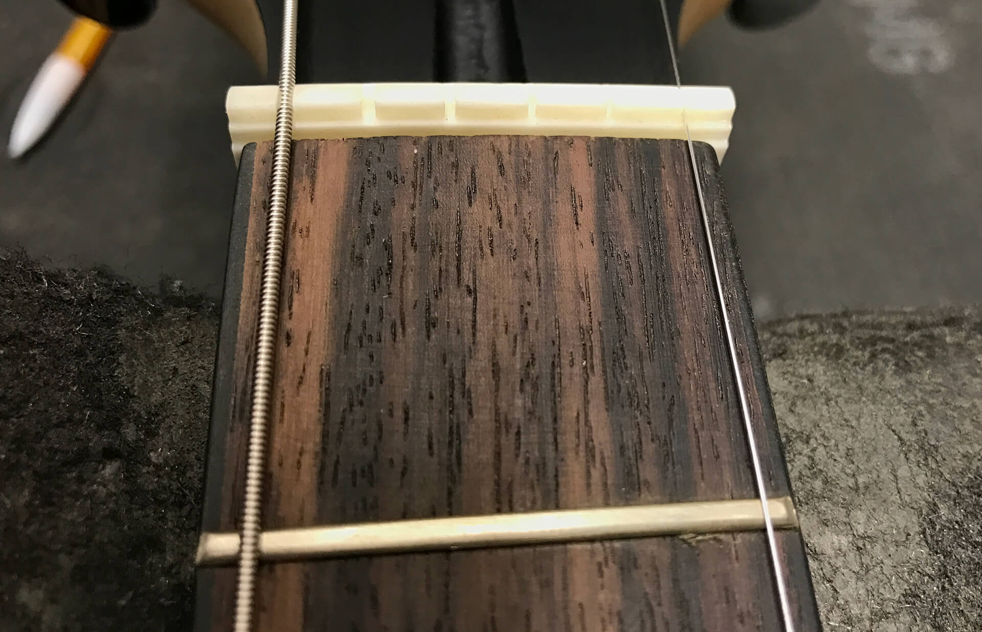 It may be helpful to place the two outside strings into the two outside slots of the nut to better visualize and determine the accurate placement.