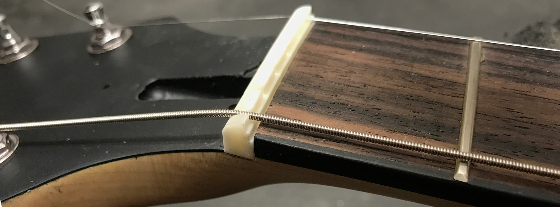 Note: The nut slot depth in the neck is not always perfectly level so sanding the bass or treble side of the Zero Glide nut more than the other may be necessary to accurately match the fingerboard.